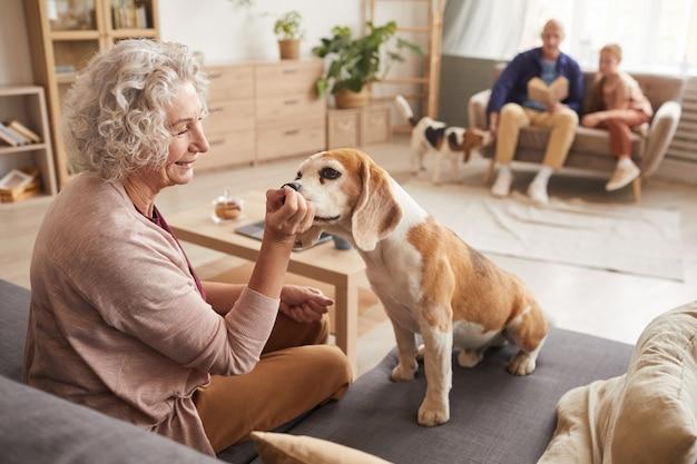 Ritratto di donna senior sorridente che gioca con il cane da compagnia amato mentre era seduto sul divano in interni domestici accoglienti con la famiglia