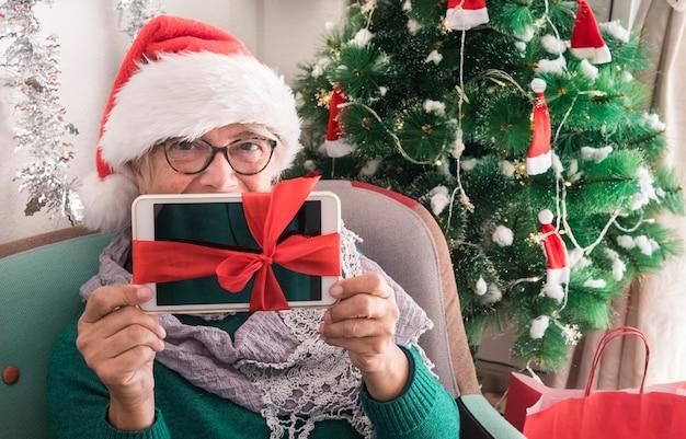 Ritratto di una donna anziana sorridente che indossa un cappello di babbo natale con in mano una tavoletta digitale come regalo di natale - buon natale a casa per un anziano pensionato che si gode le vacanze