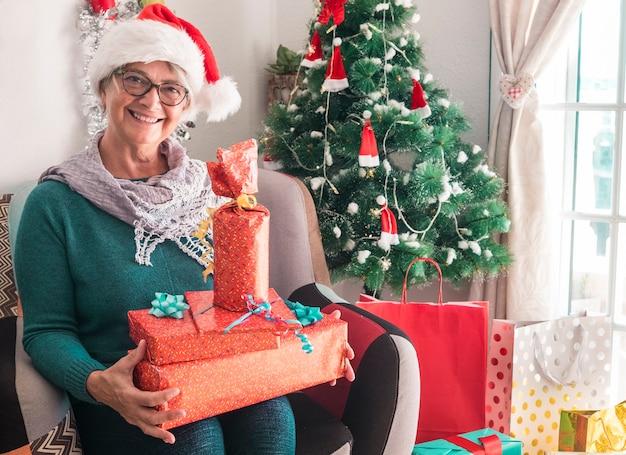 Ritratto di una donna anziana sorridente che indossa un cappello di babbo natale con molti regali di natale per la famiglia - buon natale a casa per un anziano pensionato che si gode le vacanze
