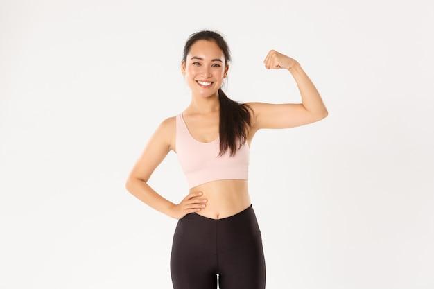Ritratto della ragazza asiatica sottile e forte sorridente di forma fisica, allenatore personale di allenamento che mostra i muscoli, flessione dei bicipiti e sguardo fiero, sfondo bianco.
