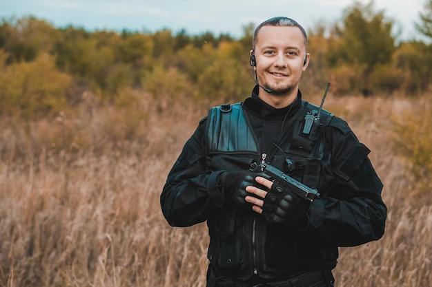 Ritratto del soldato sorridente delle forze speciali in uniforme nera con una pistola