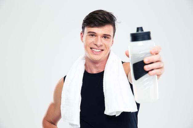 Ritratto di un uomo sportivo sorridente con un asciugamano che dà una bottiglia con acqua alla telecamera isolata
