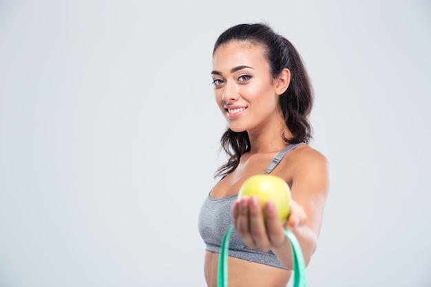 Ritratto di una donna sorridente di sport che tiene mela e tipo di misurazione isolato su un muro bianco
