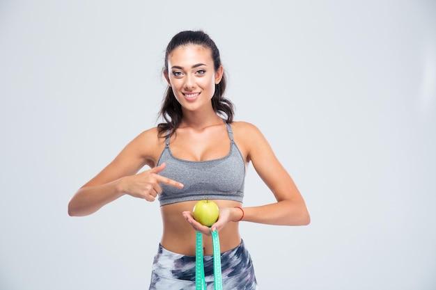 Ritratto di una donna sorridente sport puntare il dito sulla mela e tipo di misurazione isolato su un muro bianco