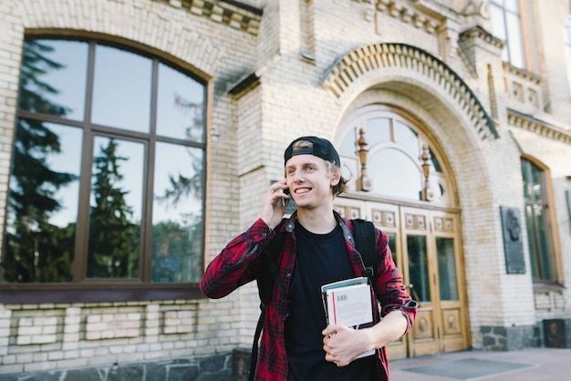 Ritratto di uno studente sorridente con i libri nelle sue mani parlando al telefono