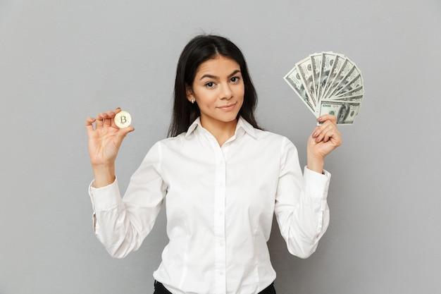 Ritratto di sorridente donna di successo con lunghi capelli castani indossando abiti da ufficio che mostra bitcoin e un sacco di soldi in valuta del dollaro, isolato sopra il muro grigio