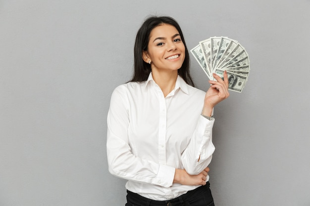 Ritratto di sorridente donna di successo con lunghi capelli castani indossando abiti da ufficio sorridente e tenendo i soldi in dollari, isolate su uno sfondo grigio