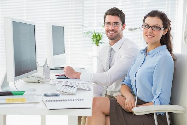 Ritratto di squadra sorridente seduto alla scrivania