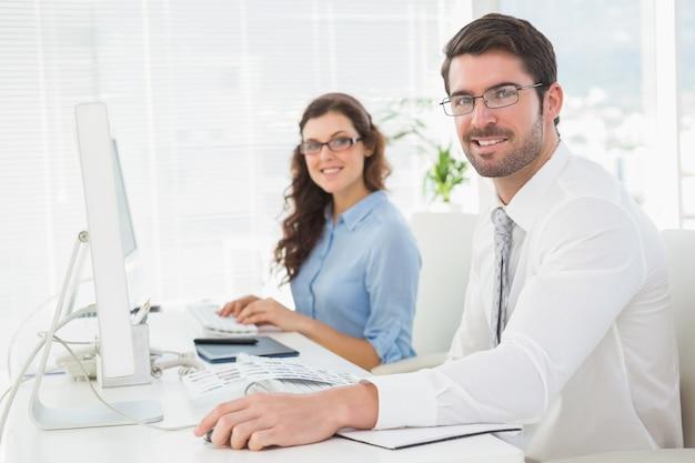 Ritratto della squadra sorridente con gli occhiali allo scrittorio