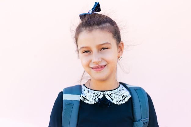 Ritratto di un'adolescente sorridente sullo sfondo del muro rosa pastello.