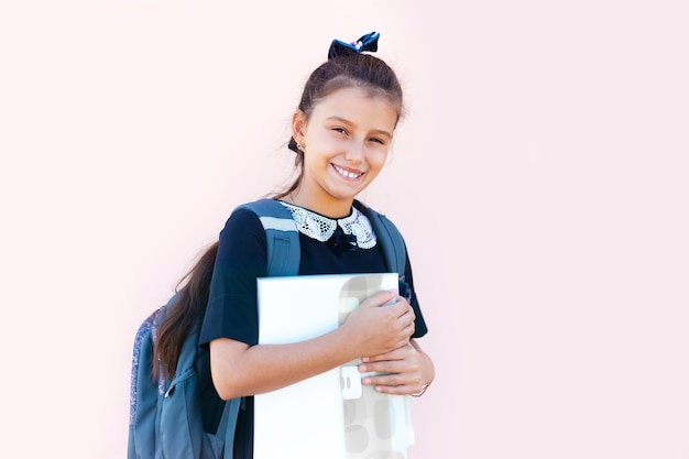 Ritratto di sorridente ragazza adolescente con zaino e libro, isolato su rosa chiaro.