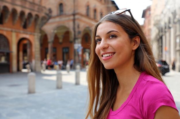 Ritratto di donna turistica sorridente visitando la città vecchia di bologna, italia