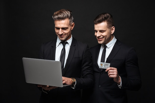 Ritratto di due uomini d'affari sorridenti vestiti in abito formale con laptop e carta di credito isolati su muro nero