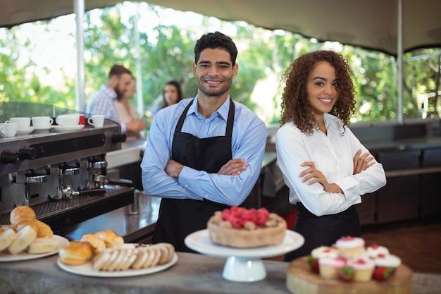 Ritratto di sorridente cameriere e cameriera in piedi con le braccia incrociate al bancone