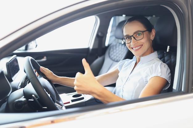 Il ritratto di una donna sorridente alla guida di un'auto nuova mostra il pollice in alto per l'acquisto di un nuovo concetto di auto