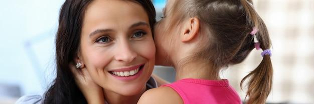 Ritratto della donna sorridente che gode passando del tempo divertente con la figlia. bambina che bisbiglia segreto in orecchio della madre felice. concetto di infanzia e famiglia