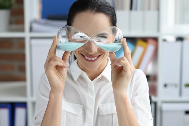 Ritratto di donna sorridente che tiene la clessidra nel controllo del tempo delle mani nel concetto di lavoro