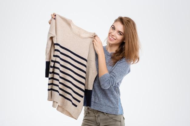 Ritratto di una donna sorridente che tiene un maglione isolato su uno sfondo bianco