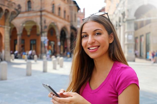 Ritratto di donna sorridente che guarda l'obbiettivo e utilizzando smart phone nella vecchia città medievale