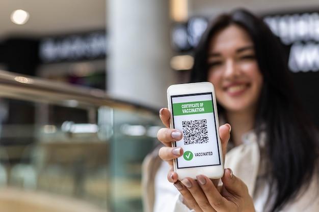 Ritratto di donna sorridente in posa con certificato di vaccino sulla prevenzione del coronavirus dello schermo dello smartphone