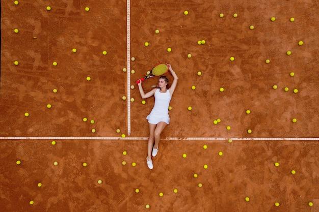 Ritratto di donna sorridente rilassante sul campo da tennis con un sacco di palle e racchetta dopo l'allenamento