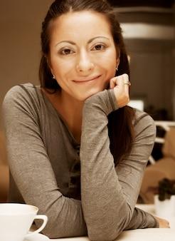Ritratto di donna sorridente appoggiato il mento a portata di mano