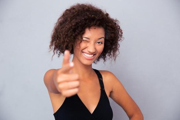 Ritratto di una donna sorridente che mostra il gesto della pistola nella parte anteriore sul muro grigio