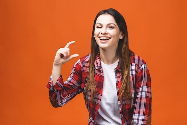 Ritratto della donna sorridente che mostra piccola quantità di qualcosa, isolato contro il fondo arancio.