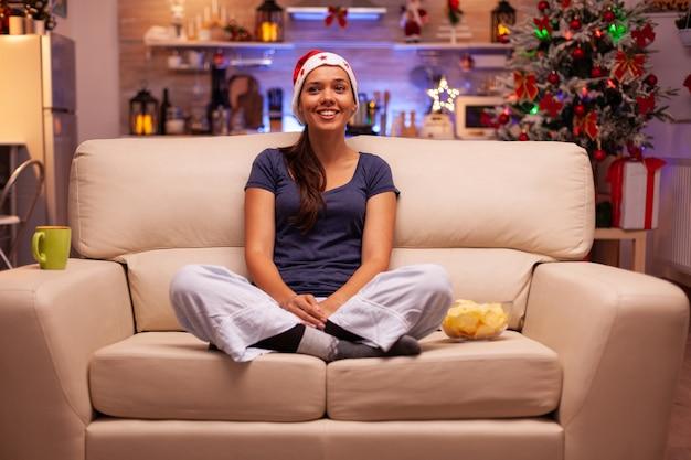 Ritratto di donna sorridente che indossa il cappello rosso di santa seduto nella posizione del loto sul divano