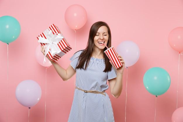 Ritratto di donna sorridente con gli occhi chiusi in abito blu che tiene scatola rossa con regalo presente bevendo soda o cola da una tazza di plastica su sfondo rosa con mongolfiere colorate. festa di compleanno.