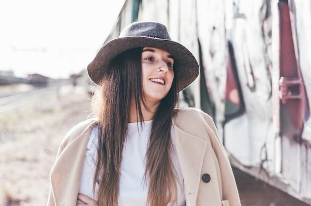 Ritratto di donna sorridente con cappello e giacca beige in una stazione ferroviaria abbandonata.