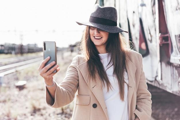 Ritratto di donna sorridente con cappello e giacca beige utilizzando il suo telefono su una stazione ferroviaria abbandonata.
