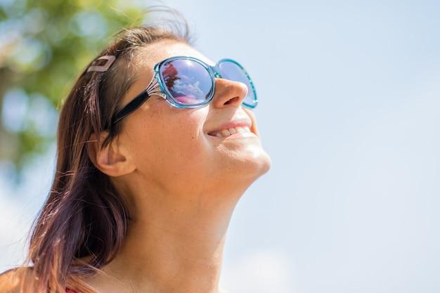 Ritratto di una donna sorridente con cappello al lago