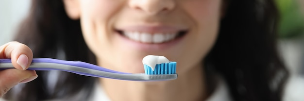 Ritratto di donna sorridente con dentifricio e pennello. concetto di sorriso bianco come la neve