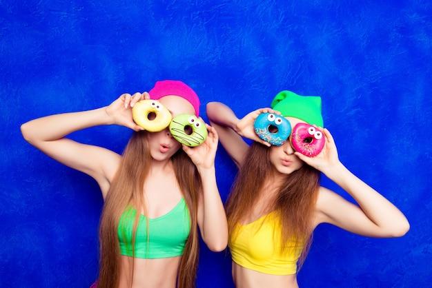 Ritratto di donne sorridenti che coprono gli occhi con ciambelle isolati su sfondo blu