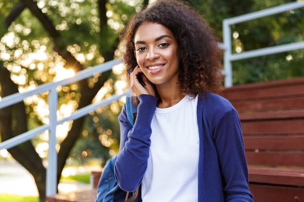 Ritratto di una giovane ragazza africana sorridente con lo zaino che parla sul telefono cellulare mentre si riposa al parco