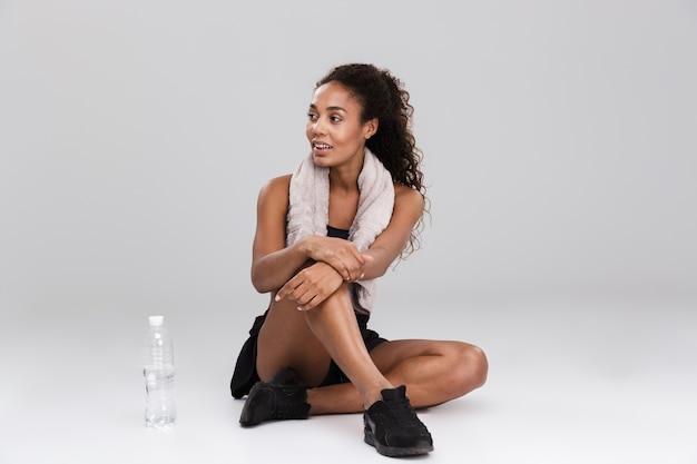 Ritratto di una giovane sportiva africana sorridente che riposa dopo l'allenamento isolato sopra il muro grigio, acqua potabile, distogliendo lo sguardo