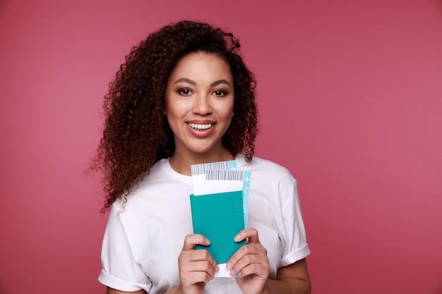 Ritratto di un sorridente giovane donna africana in possesso di passaporto e biglietti di viaggio isolato su sfondo rosa