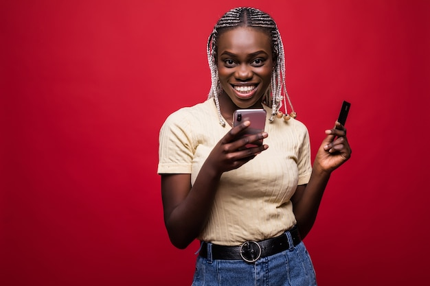 Ritratto di sorridente giovane donna africana in piedi isolato su sfondo rosso