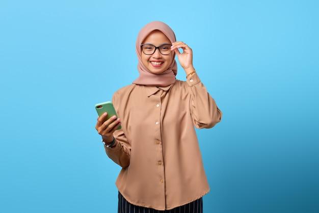 Ritratto di giovane donna asiatica sorridente che tiene smartphone e occhiali guardando la fotocamera