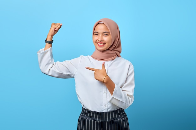 Ritratto di una giovane donna asiatica sorridente che alza la mano mostrando forza e si sente vittoria indipendente