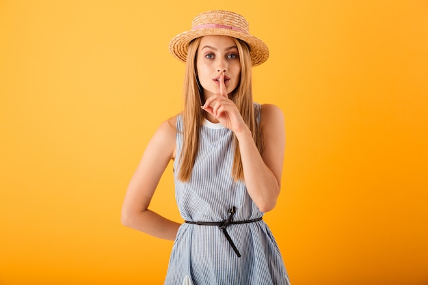 Ritratto di una giovane donna bionda sorridente in cappello estivo