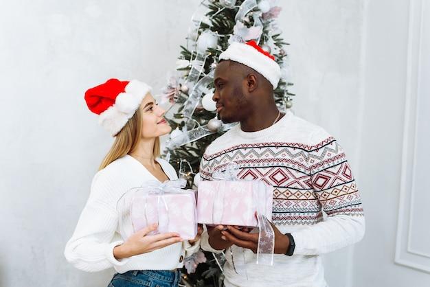 Il ritratto della giovane coppia sorridente vicino all'albero di natale celebra insieme il nuovo anno.