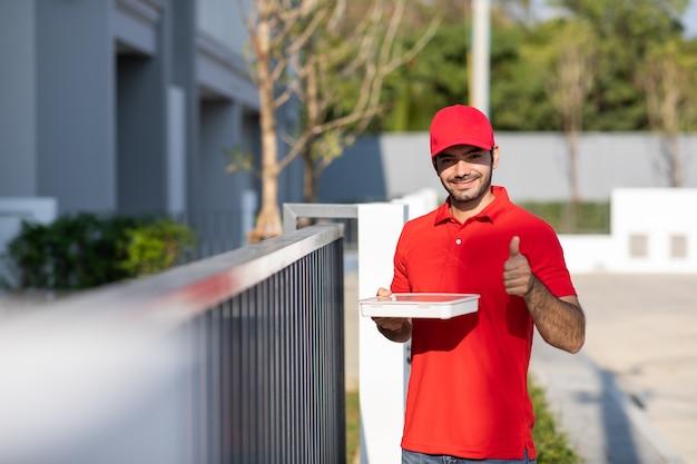 Ritratto sorridente giovane fattorino in uniforme rossa che tiene una scatola davanti alla casa.