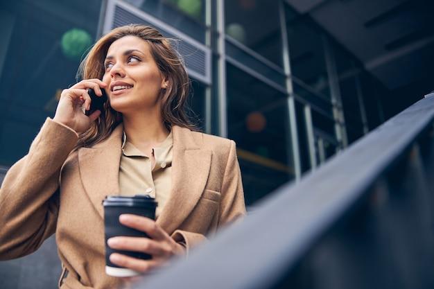 Ritratto di una giovane imprenditrice sorridente che ha una conversazione telefonica durante la pausa caffè