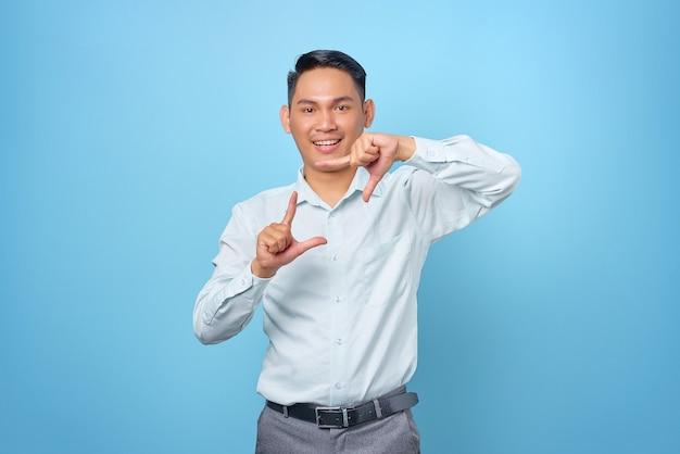 Ritratto di giovane uomo d'affari bello sorridente che fa una cornice con la mano su sfondo blu