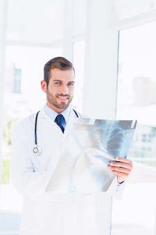 Ritratto di un giovane medico maschio sorridente che esamina raggi x