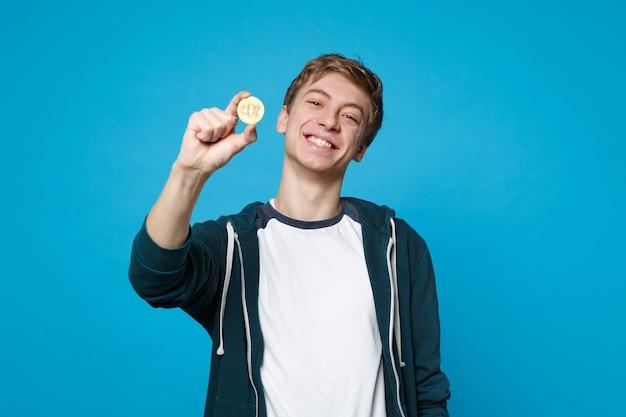 Ritratto di un giovane sorridente in abiti casual che tiene bitcoin, valuta futura isolata sulla parete blu. persone sincere emozioni, concetto di stile di vita.