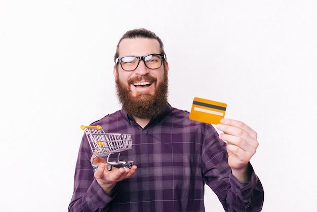 Ritratto di giovane sorridente in occhiali da vista casual e azienda piccolo carrello della spesa e carta di credito