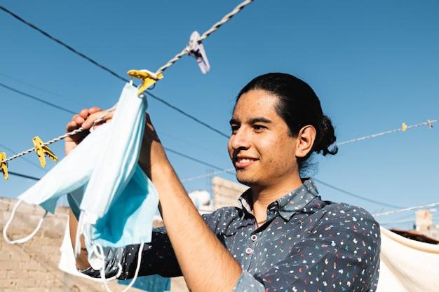 Ritratto di un giovane sorridente che appende maschere facciali blu ad asciugare al sole in cortile
